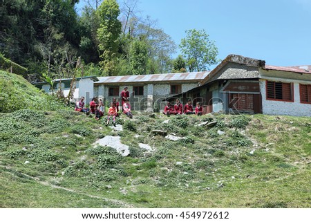 TOLKA, NEPAL - APRIL 19, 2016: nepalese young girls dressed with school uniform resting in the playground of a nepalese school in Tolka village, Nepal.