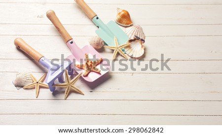 Tolls  for kids for sand and sea object on white  painted wooden background. Place for text. Toned image. - stock photo