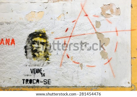 """TOMAR, PORTUGAL - APRIL 28, 2015: Che Guevara graffiti on old house wall, text in Portuguese """"for sale, for exchange"""" and anarchy symbol. In mass pop culture Che Guevara became a symbol of revolution. - stock photo"""
