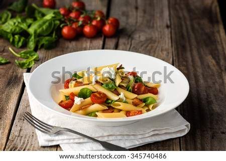 Tomato and Bacon Penne Pasta on wood table - stock photo