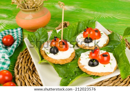 Tomato and cheese crackers decorated as ladybirds, kid food - stock photo