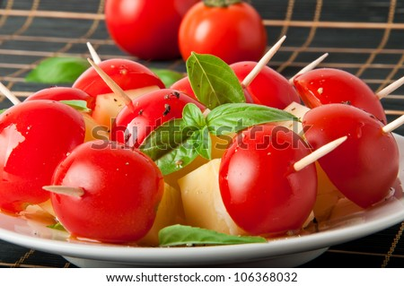 Tomato and  cheese slices decorated with basil leaves on a plate and black background