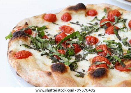 Tomato and fresh basil pizza on a white background. - stock photo