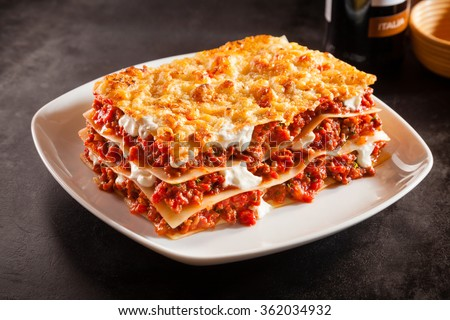 Tomato and ground beef lasagne with cheese layered between sheets of traditional Italian pasta served on a white plate on a dark restaurant or bar counter - stock photo