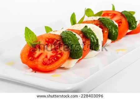 Tomato and mozzarella slices decorated with basil leaves on a plate and white background. Selective focus - stock photo
