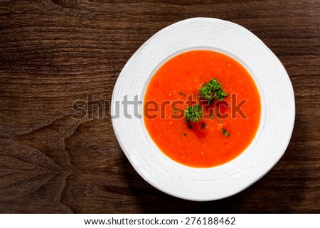 Tomato and red pepper soup in a white bowl on a dark wooden background. - stock photo