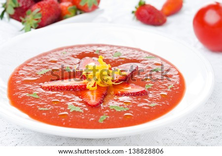 tomato and strawberry gazpacho in a plate, fresh berries and tomatoes in the background, horizontal close-up - stock photo
