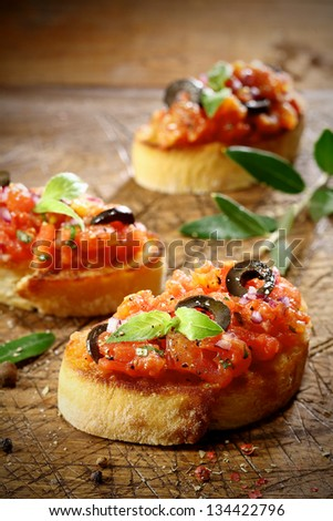 Tomato bruschetta topped with olive and basil on slices of crisp crusty toasted or grilled baguette lying on an old grunge badly scored wooden chopping board, low angle view with shallow dof - stock photo