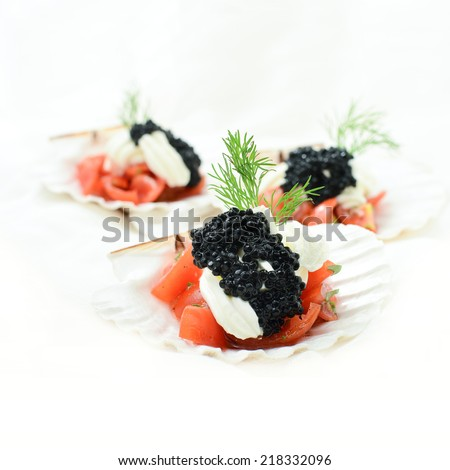 Tomato, cream cheese and caviar canapes with garnish against a white background. Copy space. - stock photo