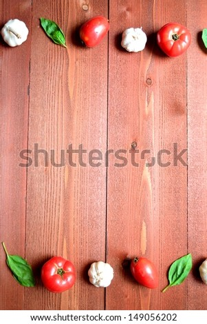 Tomato,garlic and basil leaf on brown background