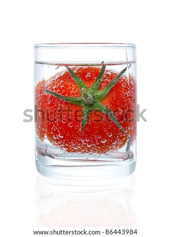 Tomato in glass of mineral water isolated on white background. Freshness and healthy lifestyle concept.