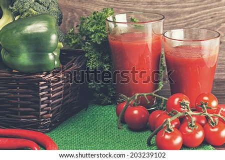 Tomato juice and basket of green vegetables - stock photo