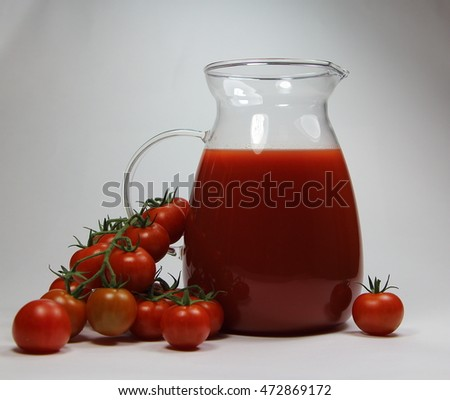 tomato juice in a jug and fresh tomato on a white table