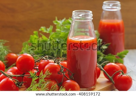 Tomato juice in bottles and fresh vegetables - stock photo