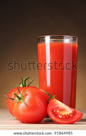 Tomato juice in glass and tomato on wooden table on brown background