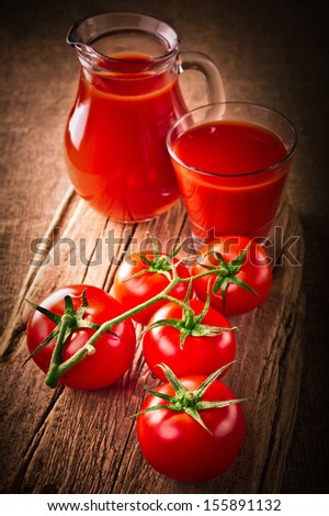 Tomato juice in glass jar and fresh organic tomatoes on wooden cutting board and linen background. Image in vintage style - stock photo