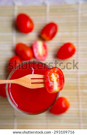 Tomato juice in glass with fresh tomato fruits - stock photo