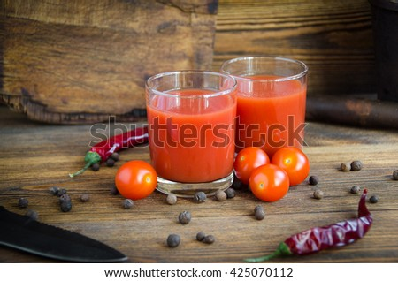 tomato juice pepper cherry on a brown wooden background with pepper and cherry - stock photo