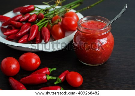 Tomato ketchup sauce with cherry tomatoes and mini red hot chili peppers in a small glass jar with a spoon on dark wooden background. Homemade tomato sauce and fresh tomatoes. Selective focus. - stock photo