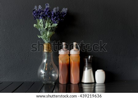 Tomato ketchup sauce with garlic, spices and herbs with cherry tomatoes in a white porcelain bowl on old wooden table, selective focus - stock photo