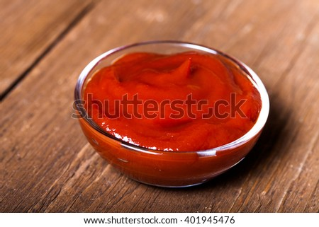 Tomato ketchup served in a small glass bowl on the old wooden table. Selective focus. Toned. - stock photo