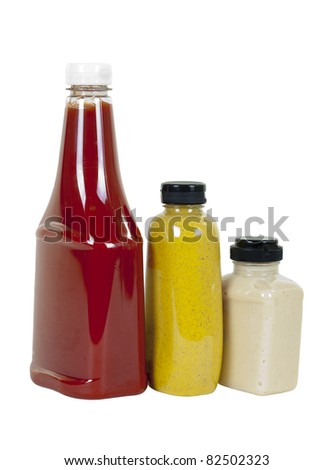 Tomato ketchup, spicy brown mustard and creamy horseradish in bottles, angle view; isolated on white background - stock photo