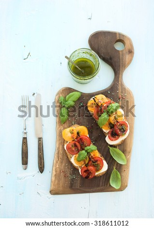 Tomato, mozzarella and basil sandwiches on dark wooden chopping board, pesto jar, dinnerware over light blue background, top view - stock photo