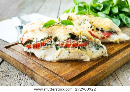 Tomato, mozzarella and basil stuffed chicken breasts  on rustic wooden table - stock photo