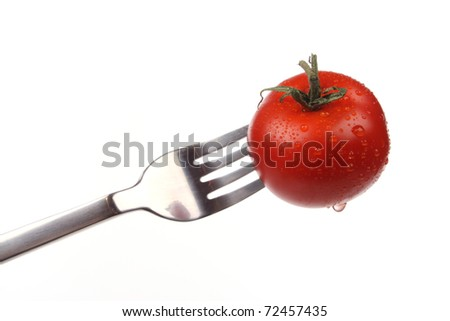 Tomato  on a fork isolated over white background