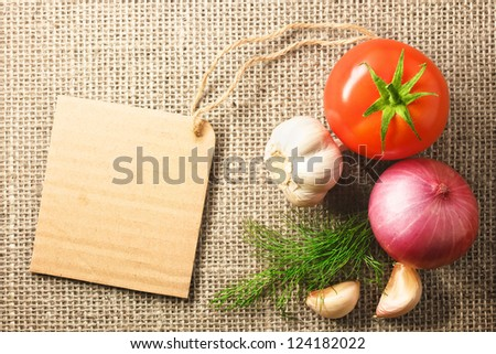 tomato onion and garlic vegetables and price tag on sacking background texture