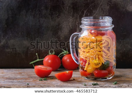 Tomato pasta with sauce, thyme and sliced cherry tomatoes in glass mason jar, served over old dark wooden background. Lunch to go.
