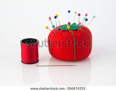 Tomato pin cushion and  thread needle - stock photo