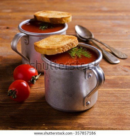 Tomato puree soup  in a metal bowl on a wooden background. Selective focus. - stock photo