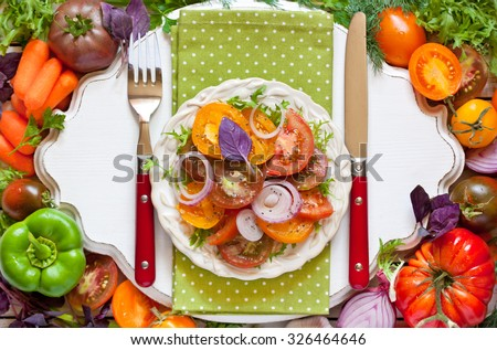Tomato salad and fresh vegetables and herbs for cooking.