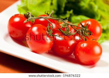 Tomato salad on a plate on a wooden table