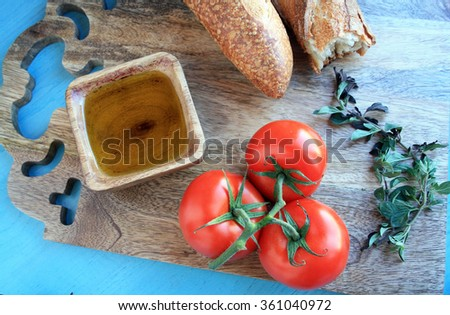 tomato sauce ingredients sauce tomatoes on the vine fresh oregano Italian bread olive oil in a wooden bowl on  a wooden cutting board with a green wooden background  - stock photo