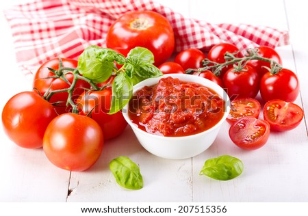 tomato sauce with fresh vegetables on wooden table - stock photo