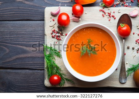 Tomato soup and fresh tomatoes on a wooden background - stock photo
