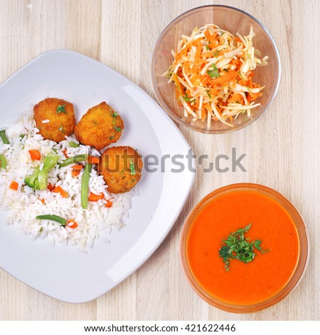 Tomato soup, coleslaw salad in glass bowls and plate with rice with chicken nugets and vegetables on rustic wooden table. top view - stock photo