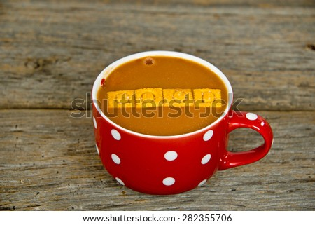 tomato soup with cheese crackers in a red soup bowl with white polka dots on rustic wood - stock photo