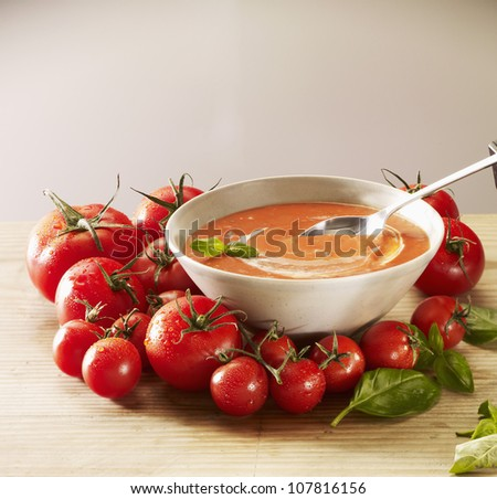 Tomato soup with cream and basil - stock photo