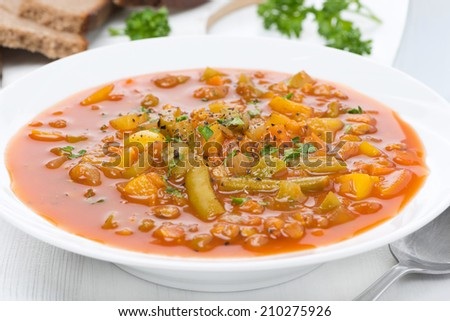 tomato soup with green lentils and vegetables, close-up, horizontal - stock photo