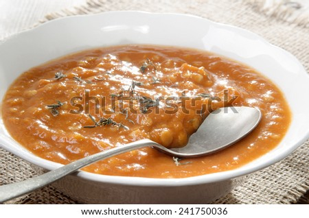 tomato soup with lentils, plate and spoon - stock photo