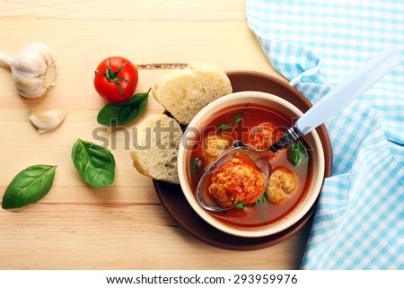Tomato soup with meat balls on wooden spoon on wooden background - stock photo