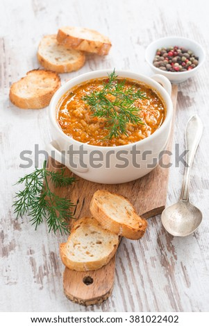 tomato soup with rice and vegetables in a saucepan and bread, vertical, top view - stock photo