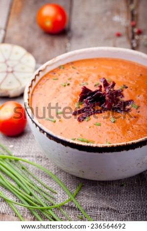 Tomato soup with sun dried tomatoes on a wooden background - stock photo