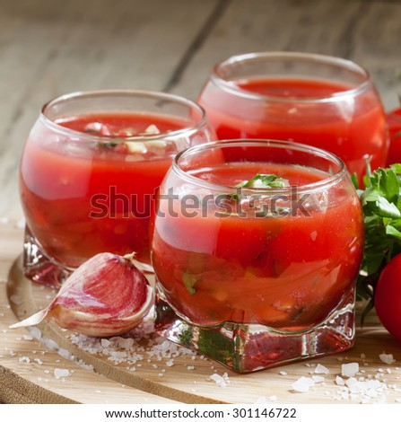Tomato soup with vegetables in a round glass bowl, selective focus - stock photo