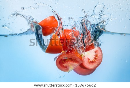 tomato splash deeply into the water - stock photo