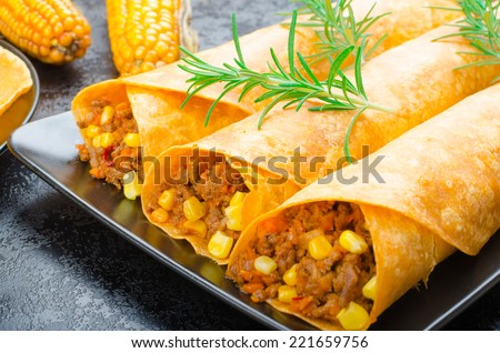 Tomato tortilla with spicy meat mixture, jalapeno, thyme and corn - stock photo