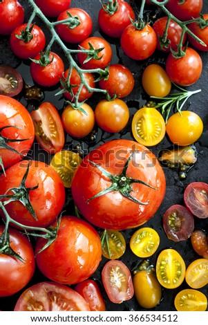 Tomato varieties on black iron.  Overhead view. - stock photo